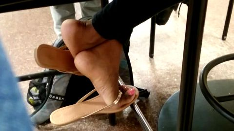 Delicious ebony girl sitting in cafeteria and exposing her lovely voyeur feet