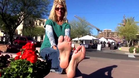 Old passionate lady takes socks off and shows her naked feet in public
