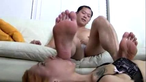 Tattooed female foot slave licking her master's toes on the floor
