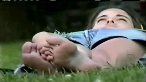 Fantastic teen girl laying on the grass outdoors showing her sexy voyeur feet