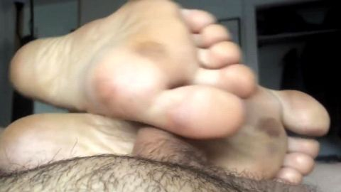 Girl with dirty amateur feet giving a footjob to a small dick in bed