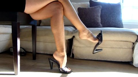 Super attractive secretary in sexy outfit sitting and playing with her shoes