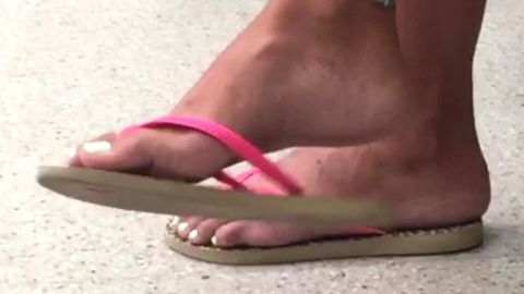 Passionate girl with cute feet wearing flip flops in public and she loves it