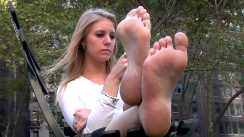 Smoking hot blonde puts her sexy voyeur feet in the air outdoors