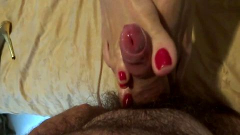 Lovely amateur feet with red nail polish giving a perfect footjob