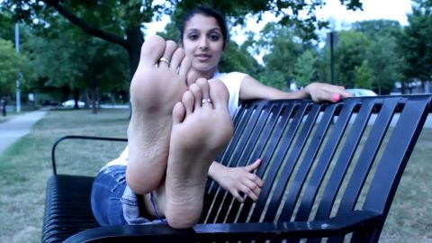 Beautiful amateur girl showing her sexy feet and toe rings at the park