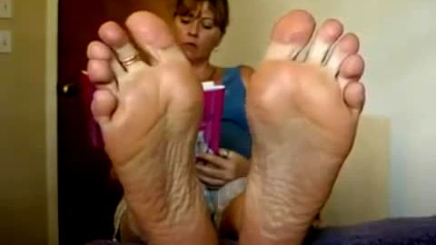 Wild MILF likes talking on the phone while exposing her feet on the camera