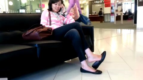 Cute Asian girl in tight jeans playing with her shoe and dangling at the shopping mall