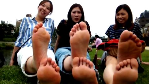 Cute Asian teenage girls sitting on the grass and showing their perfect feet in public