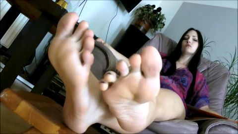 Wonderful brunette exposes her delicious soles as reading a magazine on the couch