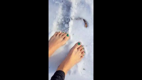 Brave girl with wonderful feet walking barefoot in the snow and she loving it