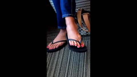 Amateur girl in sexy tight jeans wearing flip flops on her soft feet with red nail polish