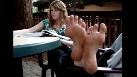Lovely college girl shows off her dirty feet and soles as she studying outdoors
