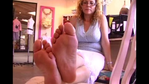 Blonde lady with glasses exposing her beautiful mature feet and soles at the furniture store