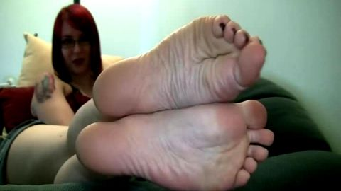 Super sexy redhead with glasses is on her side exposing her amateur feet