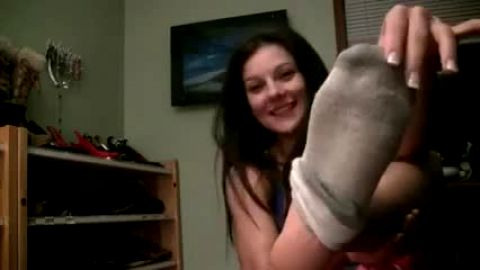 Sweet girl takes her dirty socks off and exposes her feet to the camera