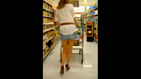 Stunning blonde loves wearing short jeans skirt and high heels while buying groceries