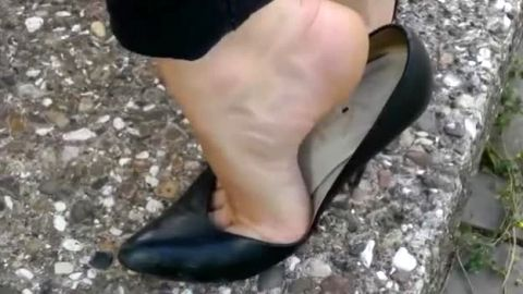 Lady in sexy jeans playing with her black high heel shoes in public