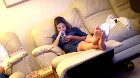 Hot MILF texting on the phone while sitting on the sofa with sexy feet in the air