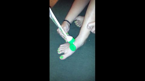 Amateur girl putting cream on her lovely feet with interesting green nail polish