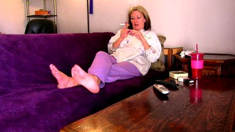 Lady with beautiful soft mature feet chilling on the sofa and smoking cigarette