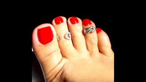 Amateur woman showing her beautiful toes with red nail polish before going out
