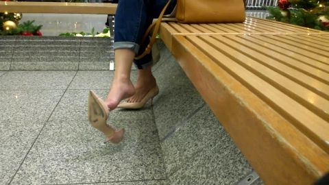 Wonderful lady in sexy jeans resting her amazing feet and dangling her shoe