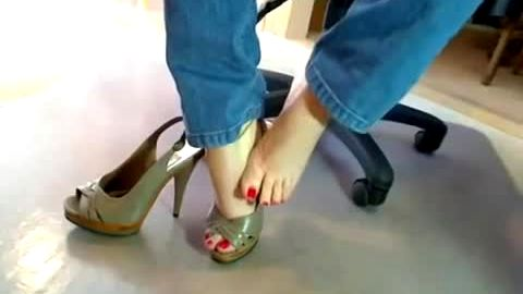 Naughty girl in jeans takes her high heel shoes off and touches her amazing feet