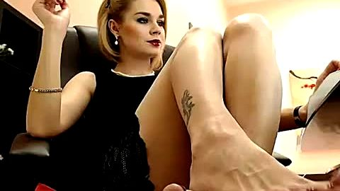 Hot blonde mistress Aisha shows off her phenomenal feet as she smokes in front of her camera