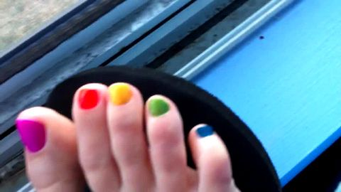Sweet amateur girl showing her colorful toe nails early morning