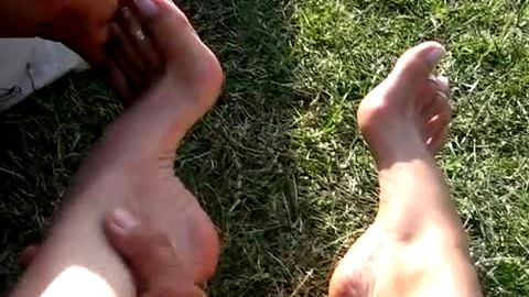 Gorgeous woman lets her man touch her beautiful feet and soles outdoors