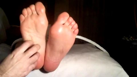 Cute amateur woman gets her fabulous feet worshipped and tickled in bed