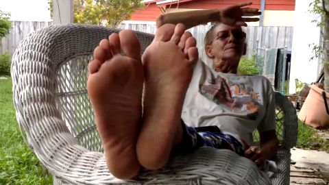 Cute granny taking dirty socks off and showing her lovely mature feet outdoors