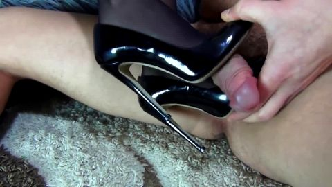 Hot brunette in stockings gives strokes a cock with her stiletto shoes until she gets jizz on them