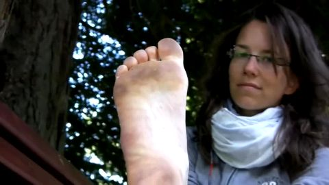 French lady with glasses sitting on the bench in the park and exposing her dirty mature soles