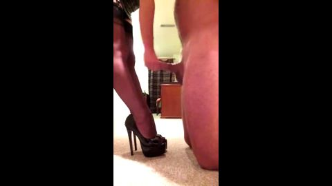 Super sexy lady in stockings and hot high heel shoes giving a handjob to a naked guy
