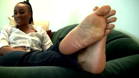 Black goddess sitting on the sofa in sexy jeans and rubbing her amazing feet