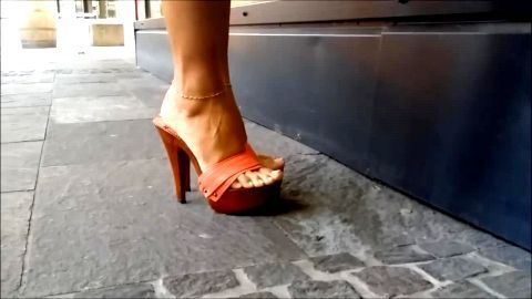 Woman with attractive legs and perfect feet walking down town in sexy mules