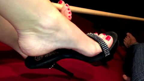 Bored amateur lady with pretty foot dangling her black shoe with high heel