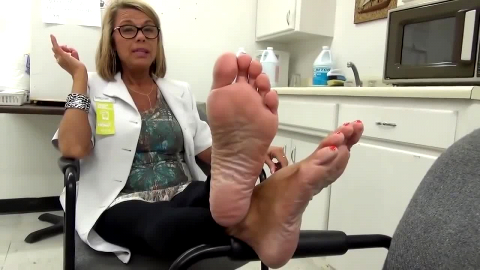 Fantastic MILF with sexy glasses resting her wonderful mature feet at the office
