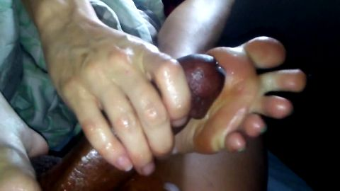 Amateur whore wanks a nasty black dick with her sexy oily feet in bed