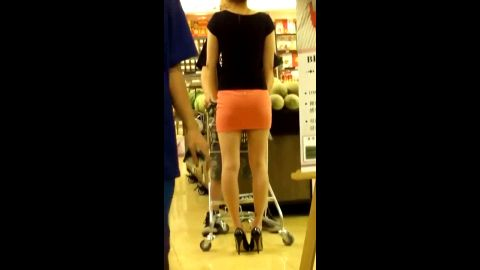 Cute Asian girl wears sexy short skirt and high heels at the super market