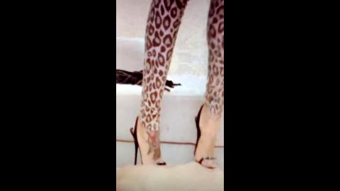 Woman in sexy leopard outfit and high heels trampling her male slave