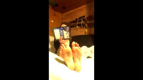 Amateur woman covers her face while playing with her incredible feet in bed