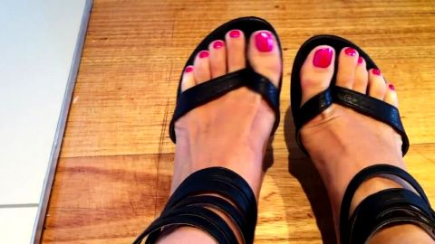 Hottie with sexy feet and pink toe nail polish wearing black sandals