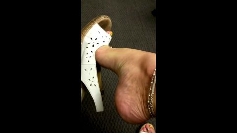 Hot lady with huge arches dangling her shoe at the office