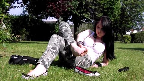 Sweet teenage brunette takes her shoes off in the nature and exposes her feet