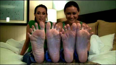 Two sexy dark haired MILFs compare each other's lovely feet in bed