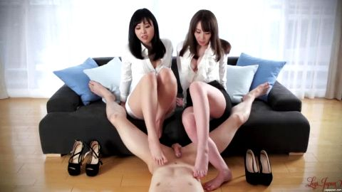 Two kinky Japanese mistresses in sexy uniforms giving a footjob to their male slave