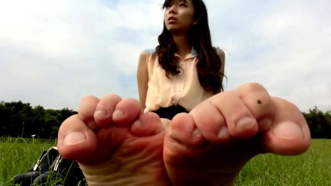 Beautiful Asian teenage girl sitting on the grass playing with her feet
